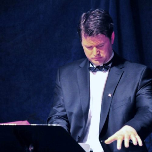 """Les Loges de la Folie chauffent la salle avec deux chansons : """"Le Véné aussi"""" (comme Félicie) interprété par Olivier. et """"Tromprettes de l'Unicité"""" (comme celles de la Renommée) interprété par Yves.    Au piano des Loges de la Folie : Paul."""